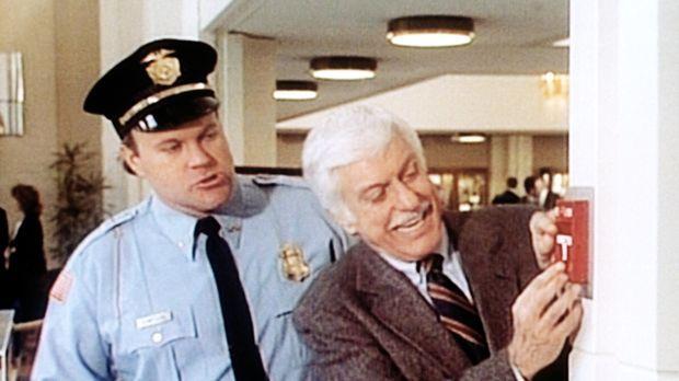 Dr. Sloan (Dick Van Dyke, r.) löst zum Schrecken der Sicherheitsleute einen F...