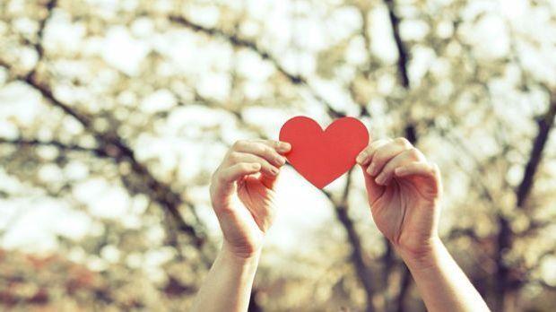 Hände, die nach einem Herz greifen