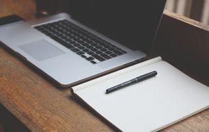 Laptop, Schreibblock und Stift
