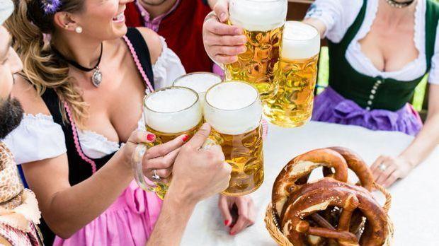 Anstoßen mit mehreren Mass Bier im bayerischen Biergarten